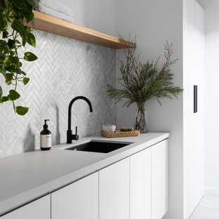 Inspiration for a large contemporary galley dedicated laundry room in Melbourne with an undermount sink, flat-panel cabinets, white cabinets, quartz benchtops, grey splashback, ceramic splashback, white walls, ceramic floors, grey floor and grey benchtop.