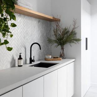 Idéer för att renovera en stor funkis grå parallell grått tvättstuga enbart för tvätt, med en undermonterad diskho, släta luckor, vita skåp, bänkskiva i kvarts, grått stänkskydd, stänkskydd i keramik, vita väggar, klinkergolv i keramik och grått golv