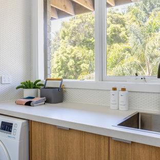 Immagine di una piccola sala lavanderia scandinava con lavello da incasso, nessun'anta, ante in legno chiaro, top in quarzo composito, pareti bianche, pavimento in legno massello medio, lavatrice e asciugatrice affiancate e top bianco