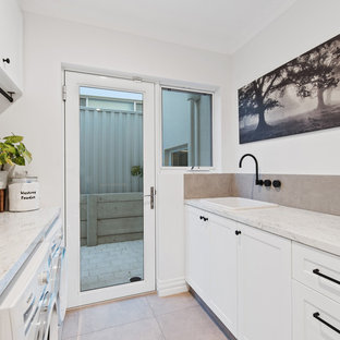 Photo of a contemporary galley laundry room in Perth with a drop-in sink, shaker cabinets, white cabinets, white walls, a side-by-side washer and dryer, beige floor and beige benchtop.
