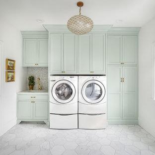Cette photo montre une buanderie linéaire chic avec un évier encastré, un placard à porte shaker, des portes de placards vertess, un mur blanc, des machines côte à côte et un sol blanc.