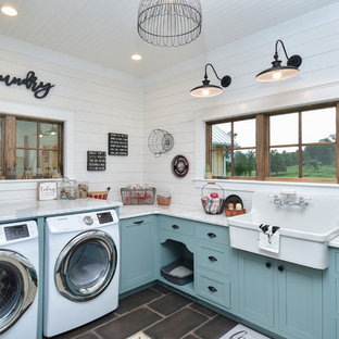 Country u-shaped porcelain floor and black floor utility room photo in Other with a farmhouse sink, shaker cabinets, blue cabinets, marble countertops, white walls, an integrated washer/dryer and white countertops