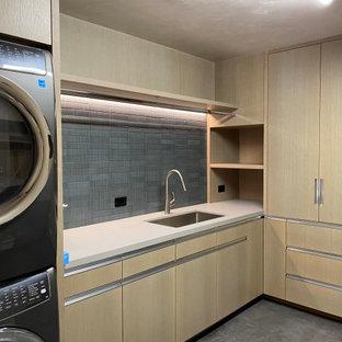 Exempel på en mellanstor modern vita l-formad vitt tvättstuga enbart för tvätt, med en enkel diskho, släta luckor, skåp i ljust trä, grått stänkskydd, stänkskydd i stenkakel, betonggolv, en tvättpelare och grått golv