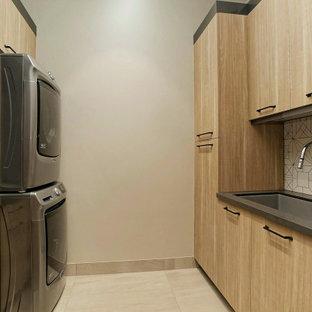 Idée de décoration pour une buanderie parallèle chalet dédiée avec un évier encastré, un placard à porte plane, des portes de placard en bois clair, une crédence multicolore, un mur beige, des machines superposées, un sol beige et un plan de travail gris.