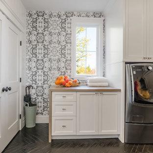 Ejemplo de lavadero multiusos, ecléctico, de tamaño medio, con armarios con paneles empotrados, puertas de armario blancas, encimera de madera, paredes blancas, suelo de madera oscura, lavadora y secadora juntas, suelo negro y encimeras marrones