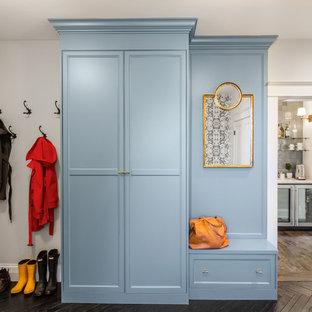 Ejemplo de lavadero multiusos, ecléctico, de tamaño medio, con armarios con paneles empotrados, puertas de armario azules, encimera de madera, suelo de madera oscura, lavadora y secadora juntas, suelo negro, encimeras marrones y paredes grises