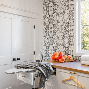 Ejemplo de lavadero multiusos, bohemio, de tamaño medio, con armarios con paneles empotrados, puertas de armario blancas, encimera de madera, paredes blancas, suelo de madera oscura, lavadora y secadora juntas, suelo negro y encimeras marrones