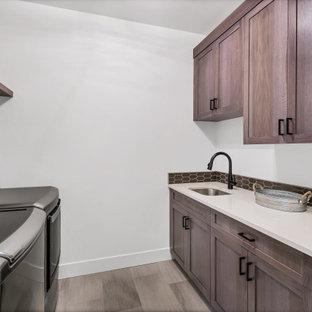 Bild på en mellanstor funkis grå parallell grått tvättstuga enbart för tvätt, med en nedsänkt diskho, skåp i shakerstil, grå skåp, bänkskiva i kvarts, svart stänkskydd, stänkskydd i keramik, vita väggar, klinkergolv i keramik, en tvättmaskin och torktumlare bredvid varandra och grått golv