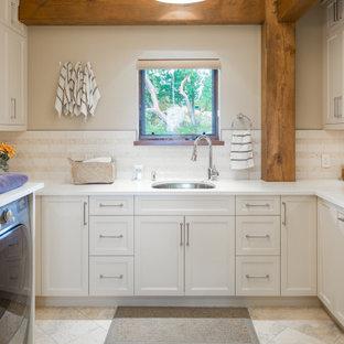 Foto di una lavanderia rustica con lavello sottopiano, ante con riquadro incassato, ante beige, pareti grigie, lavatrice e asciugatrice affiancate, pavimento beige e top bianco