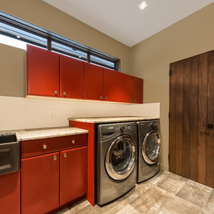 This is an example of a large rustic utility room in Vancouver with a belfast sink, flat-panel cabinets, red cabinets, granite worktops, beige walls, porcelain flooring and a side by side washer and dryer.