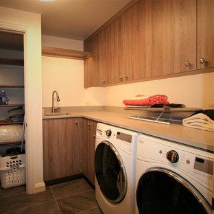 Idee per una sala lavanderia minimal di medie dimensioni con lavello sottopiano, ante lisce, ante in legno scuro, top in cemento, lavatrice e asciugatrice affiancate, pareti beige e pavimento con piastrelle in ceramica