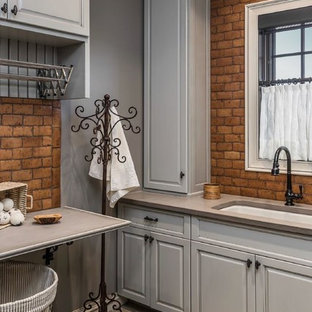 Inspiration for a rustic dedicated laundry room remodel in Other with an undermount sink, raised-panel cabinets, gray cabinets, gray walls and gray countertops