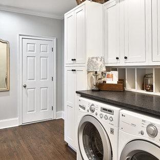 Esempio di una sala lavanderia country di medie dimensioni con ante in stile shaker, ante bianche, top in granito, pareti grigie, parquet scuro, lavatrice e asciugatrice affiancate, pavimento marrone e top nero