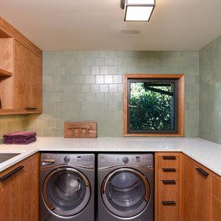 На фото: отдельная, п-образная прачечная среднего размера в современном стиле с накладной раковиной, плоскими фасадами, фасадами цвета дерева среднего тона, столешницей из переработанного стекла, зелеными стенами и со стиральной и сушильной машиной рядом с