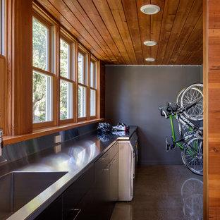 Idéer för ett mellanstort modernt linjärt grovkök, med en integrerad diskho, släta luckor, svarta skåp, bänkskiva i rostfritt stål, grå väggar, betonggolv, en tvättmaskin och torktumlare bredvid varandra och grått golv