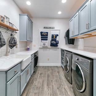 Ispirazione per una sala lavanderia tradizionale con lavello stile country, ante con riquadro incassato, ante blu, pareti bianche, lavatrice e asciugatrice affiancate, pavimento marrone e top bianco