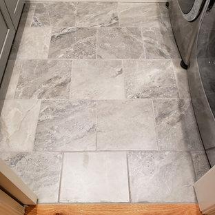 Exempel på ett stort amerikanskt parallellt grovkök, med en enkel diskho, skåp i shakerstil, granitbänkskiva, grått stänkskydd, stänkskydd i marmor, grå väggar, klinkergolv i porslin, en tvättmaskin och torktumlare bredvid varandra och grått golv