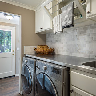 Small trendy galley dark wood floor and brown floor dedicated laundry room photo in Other with an utility sink, shaker cabinets, white cabinets, gray walls, a side-by-side washer/dryer, white countertops and stainless steel countertops