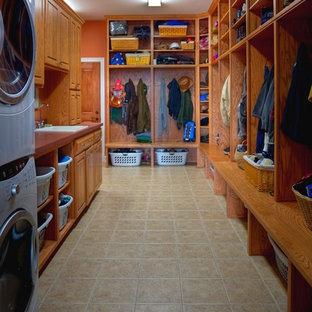 Idéer för att renovera ett mellanstort vintage parallellt grovkök, med en nedsänkt diskho, luckor med upphöjd panel, bänkskiva i koppar, orange väggar, klinkergolv i porslin, en tvättpelare och skåp i mellenmörkt trä