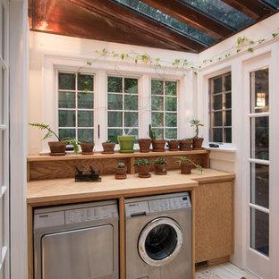 Bild på ett litet vintage beige linjärt beige grovkök, med släta luckor, skåp i ljust trä, träbänkskiva, vita väggar, travertin golv och en tvättmaskin och torktumlare bredvid varandra