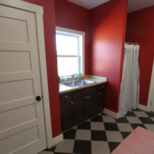 Photo of a large traditional galley utility room in DC Metro with a built-in sink, raised-panel cabinets, dark wood cabinets, laminate countertops, red walls and ceramic flooring.