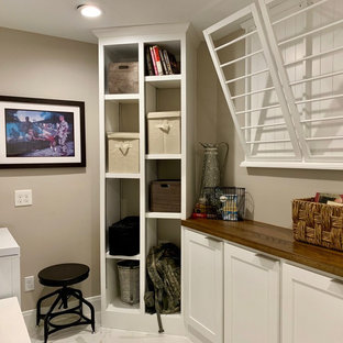 Small transitional u-shaped white floor and marble floor utility room photo in Houston with shaker cabinets, white cabinets, wood countertops, gray walls, a side-by-side washer/dryer and brown countertops