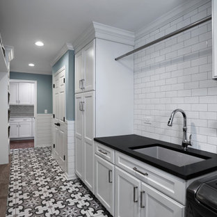This is an example of a medium sized traditional galley separated utility room in Chicago with a submerged sink, recessed-panel cabinets, white cabinets, granite worktops, blue walls, ceramic flooring, a side by side washer and dryer, multi-coloured floors and black worktops.