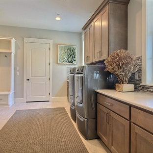 Exempel på ett mycket stort amerikanskt vit l-format vitt grovkök, med en nedsänkt diskho, släta luckor, bruna skåp, bänkskiva i kvarts, grå väggar, klinkergolv i keramik, en tvättmaskin och torktumlare bredvid varandra och beiget golv