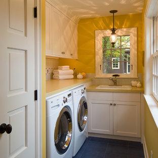 Inspiration för en liten vintage l-formad tvättstuga enbart för tvätt, med en nedsänkt diskho, vita skåp, laminatbänkskiva, gula väggar, en tvättmaskin och torktumlare bredvid varandra, klinkergolv i keramik och skåp i shakerstil