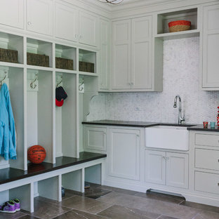 Large transitional l-shaped dedicated laundry room in Chicago with white walls, marble floors, a farmhouse sink, recessed-panel cabinets, solid surface benchtops, a concealed washer and dryer and grey cabinets.