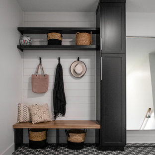 Inspiration for a large scandinavian utility room in Other with shaker cabinets, black cabinets, grey walls, ceramic flooring, a stacked washer and dryer and grey floors.