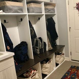 Inredning av ett klassiskt litet parallellt grovkök, med en nedsänkt diskho, släta luckor, skåp i ljust trä, träbänkskiva, grå väggar, klinkergolv i porslin, en tvättmaskin och torktumlare bredvid varandra och grått golv