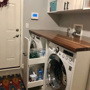 Foto di una piccola lavanderia multiuso tradizionale con lavello da incasso, ante lisce, ante in legno chiaro, top in legno, pareti grigie, pavimento in gres porcellanato, lavatrice e asciugatrice affiancate e pavimento grigio