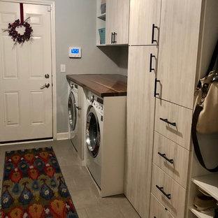 Foto på ett litet vintage parallellt grovkök, med en nedsänkt diskho, släta luckor, skåp i ljust trä, träbänkskiva, grå väggar, klinkergolv i porslin, en tvättmaskin och torktumlare bredvid varandra och grått golv