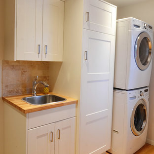Inspiration for a small transitional galley utility room in Other with a drop-in sink, shaker cabinets, white cabinets, wood benchtops, grey walls, light hardwood floors and a stacked washer and dryer.