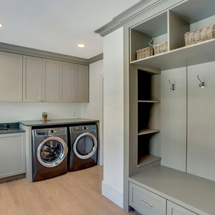 Inspiration for a large contemporary galley utility room in New York with a built-in sink, shaker cabinets, green cabinets, green walls, light hardwood flooring, a side by side washer and dryer, brown floors and black worktops.