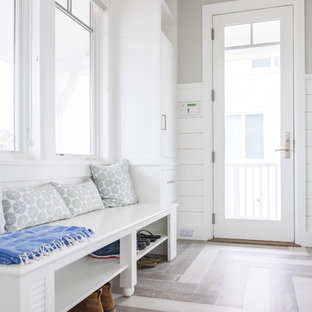 Design ideas for a mid-sized beach style l-shaped utility room in New York with louvered cabinets, white cabinets, wood benchtops, white walls, light hardwood floors, a side-by-side washer and dryer, grey floor and white benchtop.