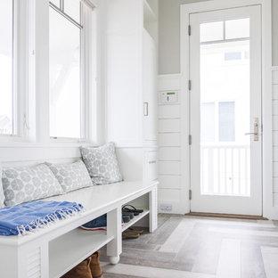 Idee per una lavanderia multiuso stile marino di medie dimensioni con ante a persiana, ante bianche, top in legno, pareti bianche, parquet chiaro, lavatrice e asciugatrice affiancate, pavimento grigio e top bianco