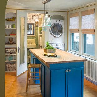 Lantlig inredning av en tvättstuga, med öppna hyllor, blå skåp, träbänkskiva och en tvättpelare
