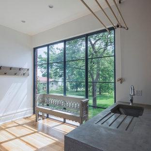 Foto di una grande lavanderia multiuso scandinava con top in cemento, lavello sottopiano, pareti bianche, parquet chiaro, lavatrice e asciugatrice affiancate e pavimento marrone