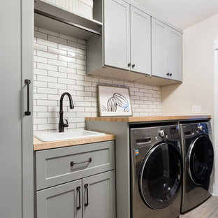 Laundry room - mid-sized modern ceramic tile laundry room idea in Chicago with a single-bowl sink, shaker cabinets, gray cabinets, wood countertops, beige walls, a side-by-side washer/dryer and beige countertops