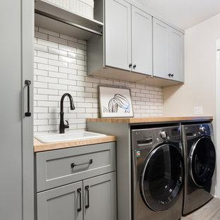 Idee per una lavanderia moderna di medie dimensioni con lavello a vasca singola, ante in stile shaker, ante grigie, top in legno, pareti beige, pavimento con piastrelle in ceramica, lavatrice e asciugatrice affiancate e top beige
