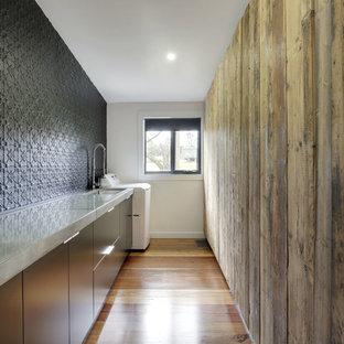 Idee per una lavanderia multiuso design di medie dimensioni con lavello sottopiano, ante lisce, ante nere, top in cemento, pareti nere e pavimento in legno massello medio