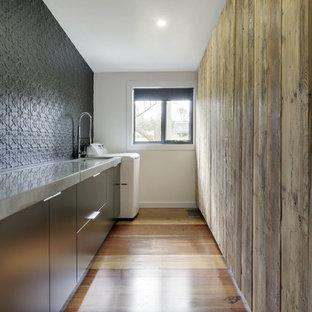 Ispirazione per una lavanderia multiuso contemporanea di medie dimensioni con lavello sottopiano, ante lisce, ante nere, top in cemento, pareti nere e pavimento in legno massello medio