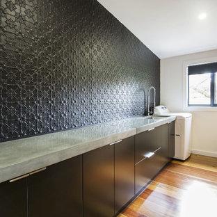 Ispirazione per una lavanderia multiuso design di medie dimensioni con lavello sottopiano, ante lisce, ante nere, top in cemento, pareti nere e pavimento in legno massello medio