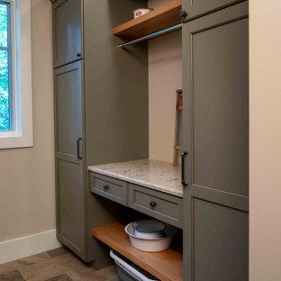 Bild på en mellanstor parallell tvättstuga enbart för tvätt, med en undermonterad diskho, luckor med infälld panel, grå skåp, flerfärgad stänkskydd, beige väggar, klinkergolv i porslin, en tvättmaskin och torktumlare bredvid varandra och flerfärgat golv