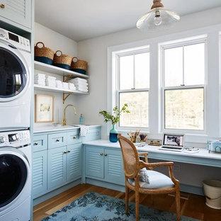 Foto di una lavanderia costiera con ante a persiana, ante blu, pavimento in legno massello medio e pavimento marrone