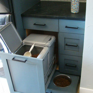 This is an example of a large transitional u-shaped utility room in Denver with shaker cabinets, blue cabinets, granite benchtops, white walls, travertine floors, a stacked washer and dryer, multi-coloured floor and black benchtop.