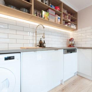 Modern inredning av ett mellanstort grå parallellt grått grovkök med garderob, med en dubbel diskho, öppna hyllor, vita skåp, bänkskiva i koppar, vitt stänkskydd, stänkskydd i tunnelbanekakel, vita väggar och ljust trägolv