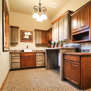 Foto di una grande lavanderia multiuso rustica con ante con bugna sagomata, ante in legno bruno, top in laminato, pareti beige, pavimento in cemento e lavatrice e asciugatrice affiancate